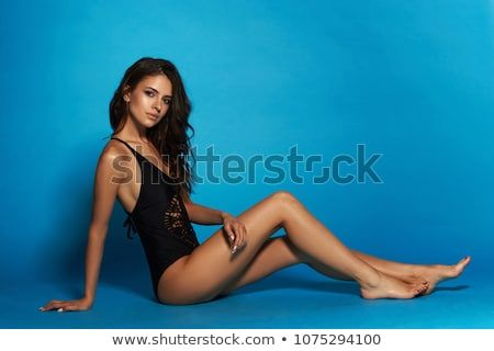 Young sexy slim tanned woman in black swimsuit posing and sitting on blue backgr...