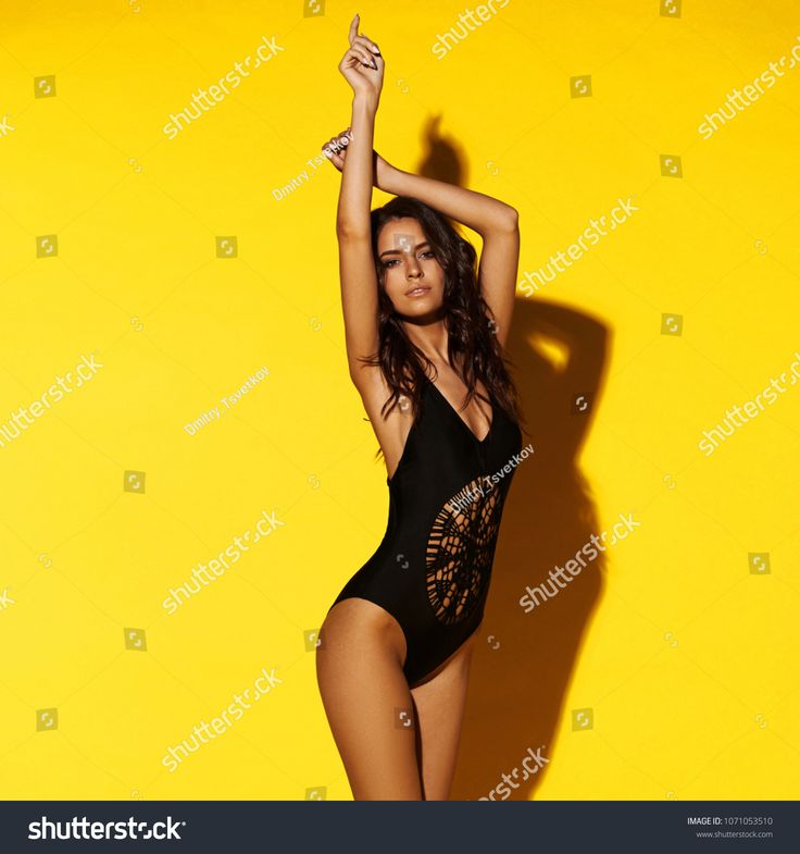 Young sexy slim tanned woman in black swimsuit posing against yellow background....