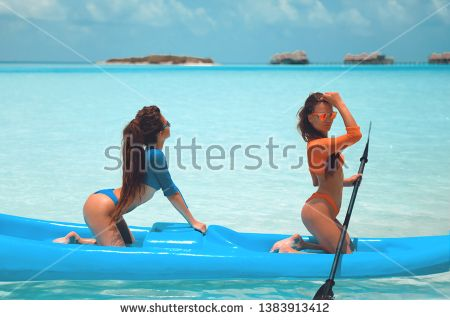 Stock Photo: Two sexy bikini models in swimwear posing on kayak, on tropical bea...
