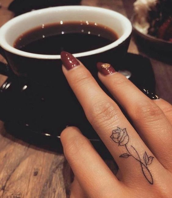 Flower tattoo on the middle finger, small rose, dark red nail polish with stones, t ...