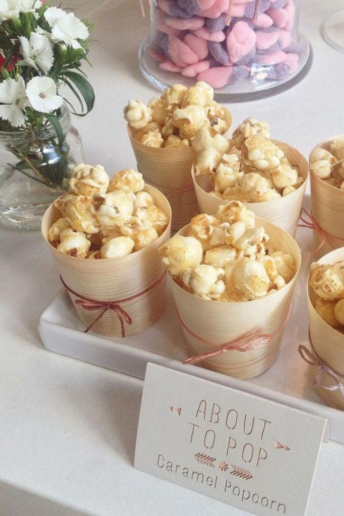 Mug with caramel popcorn, party favors Baby shower, white flowers in vase