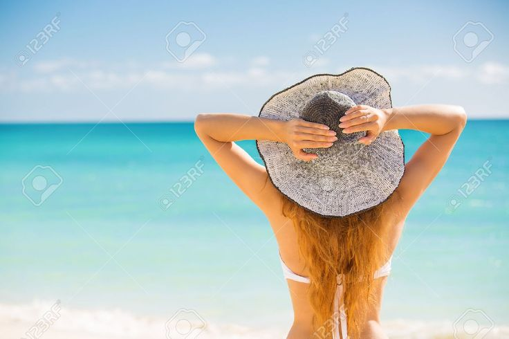 Happy young woman enjoying beach relaxing joyful in summer by tropical blue wate...