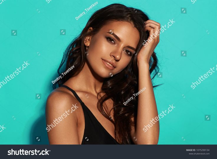 Young sexy slim tanned woman in black swimsuit posing against blue background. C...