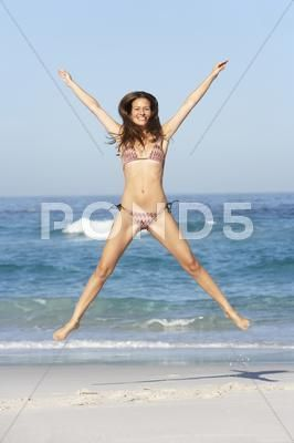 Athletic Young Woman Jumping On Sandy Beach On Holiday Wearing Bikini Stock Phot...
