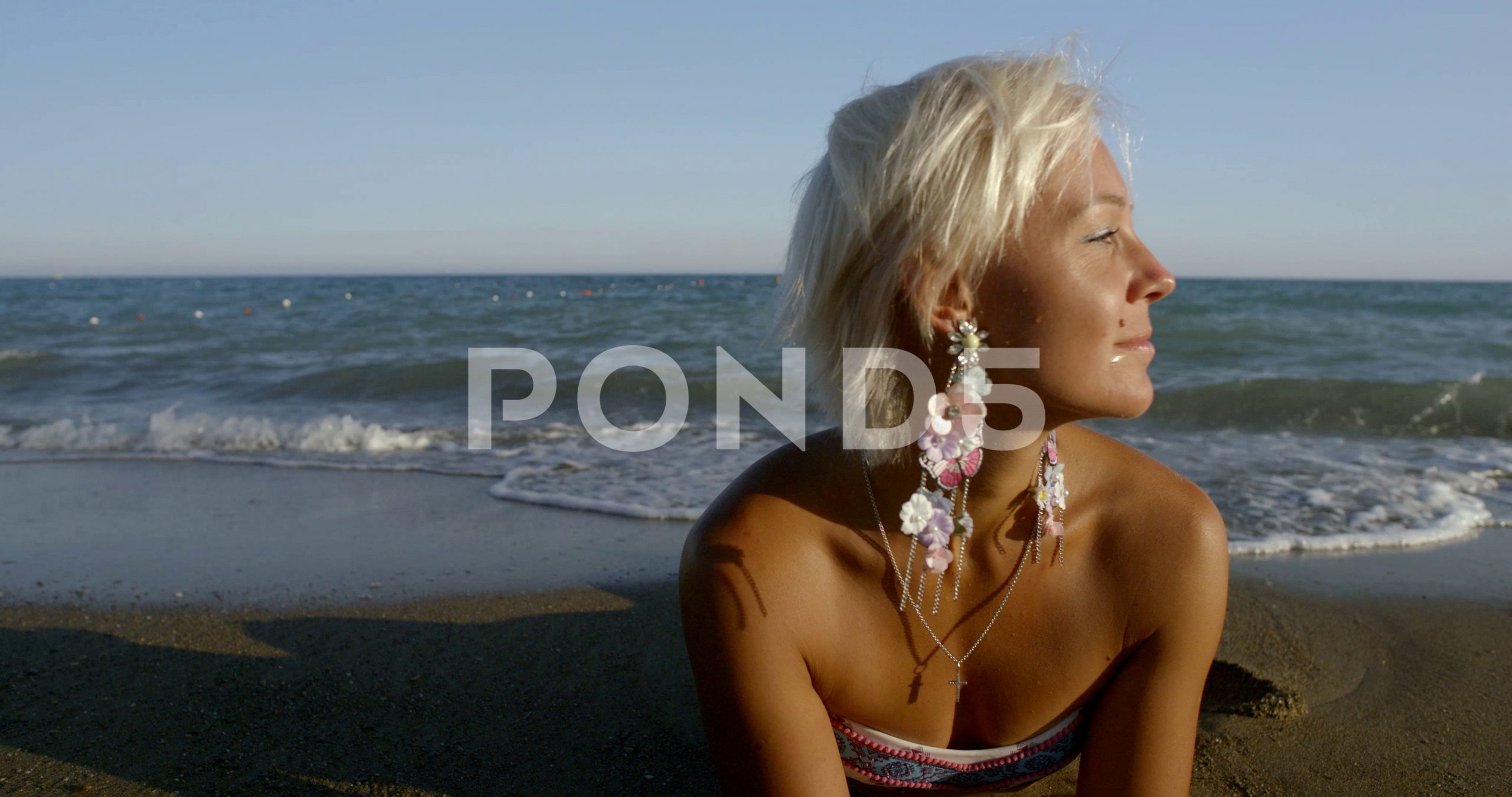 Woman relaxing on the beach in the ocean on vacation. Beautiful young bikini Sto...